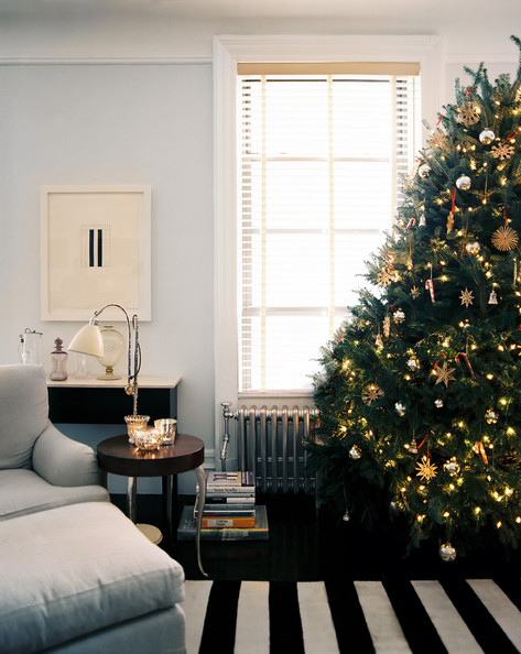 Holiday Decor - A Christmas tree beside a gray chair and ottoman and a black-and-white-striped rug