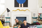An armchair and glass-topped table in the living room of designer Jonathan Adler (foreground) and Barneys New York's Simon Doonan