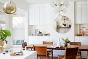 A bright dining space with white cabinets and leather dining chairs.