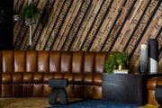 Patterned natural wood wall behind curved leather couch.