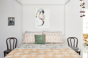 A vintage bedroom with white walls and a floral quilt.