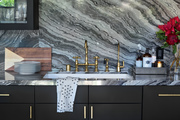 A gold sink and black marble in a contemporary kitchen.