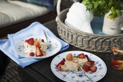 A dessert of berries plated on fluted china