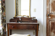 A woodsy mirror over a traditional writing desk