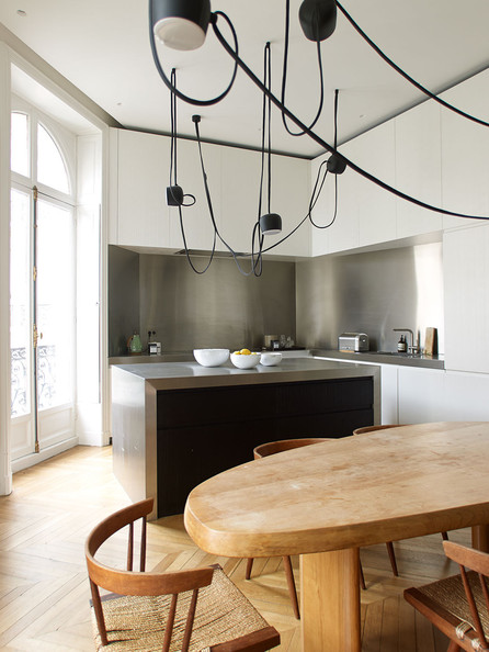 Island - A contemporary light fixture above a Charlotte Perriand table in a modern kitchen
