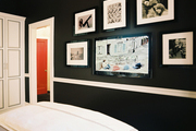 Black walls in a bedroom filled with black-and-white photographs