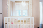 A large white mirror and a white crib in a nursery