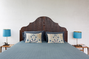 Blue bedding with a wood headboard.