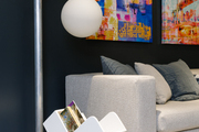 A moody living room with an artsy magazine rack and floor lamp.