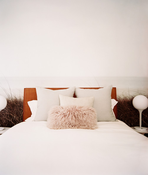 Jarlath Mellett - Neutral bedding and a vintage lamp in a room with nature-inspired wallaper