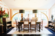 A wooden table and chairs and a pair of faux tusks in a pink paneled dining space