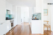 Contemporary white and blue kitchen with wooden floors.