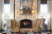 A pair of stately armchairs in front of a fireplace