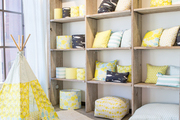 Small tipi and matching throw pillows on natural wooden shelving.