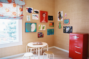 Grass-cloth wallpaper hung with children's art in a playroom