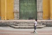 A boy rollerblades in front of a church facade in an empty plaza in Cartagena, Colombia.