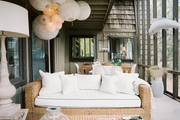 A grouping of paper lanterns hung above a woven couch with white cushions