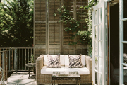 French doors leading to a patio with a wicker couch and a zebra hide