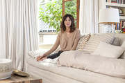Stephanie Schur ensconced on a pillow-laden sofa