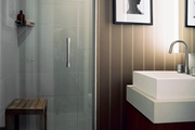 A wooden stool in a shower and striped walls in a bathroom