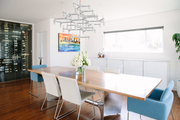 A wooden dining table and accent chairs in a white room with a modern light fixture and a wine fridge.