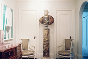 A pair of upholstered chairs flanking a marble column topped with a bust