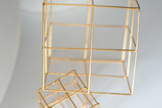 Small gold sculpture atop white tabletop.