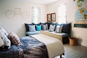 A blue corner bench and a wall map in a bedroom filled with patterns