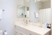 A contemporary bathroom with white cabinets and walls.