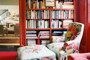 A floral chair and ottoman in a sitting room with red walls and brass sconces