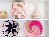 A white bookshelf with pink, woven baskets.