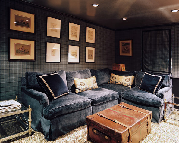 Living Room - A blue sectional couch and a leather trunk atop leopard-print carpeting