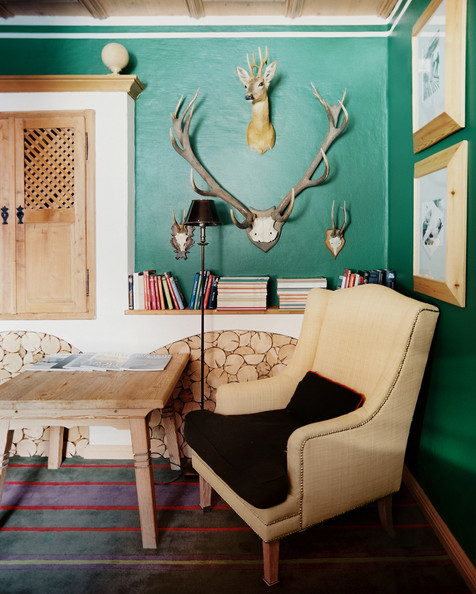 Living Room - A nailhead-trimmed armchair in the corner of a room with green walls