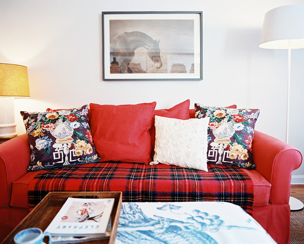 Lizzie Bailey - A red couch topped with floral pillows and a plaid throw