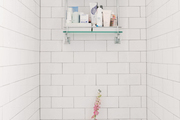 A tiled bathroom with beauty products and a floral arrangement.