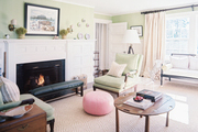 A pair of green armchairs and a pink pouf in an open living space
