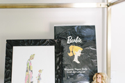 This shelf features Barbie and associated art.
