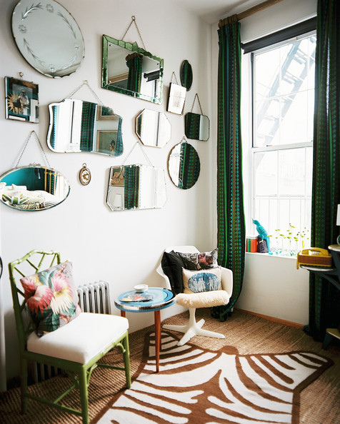 Mirror Display - A grouping of mirrors hung above a room with a zebra-print rug and green patterned curtains