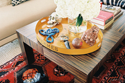Layered rugs beneath a rectangular coffee table topped with an Hermes tray