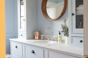 Round mirror above marble countertop and large drawers.