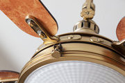 A burled wood ceiling fan trimmed in antiqued brass