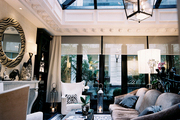A glass ceiling and a black lantern in a living space with white wingback chairs