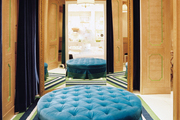 A tufted blue ottoman in a wood-paneled dressing room