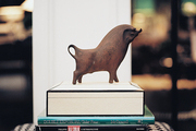 A wooden animal figurine and a stack of books atop a houndstooth-patterned stool