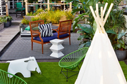 A rooftop patio with a dining area, seating area, and kids play area with a tepee