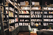 Bedding, throw pillows, and other home accessories arranged on gray built-in shelving