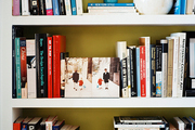 Books and decorative accessories on white shelves with a green background