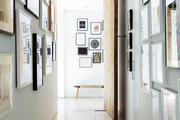 A bench amid a hallway's gallery walls hung with framed art