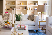 Built in shelving behind large white couches with patterned throw pillows.