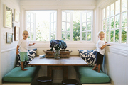 A banquette with green cushions in a breakfast nook